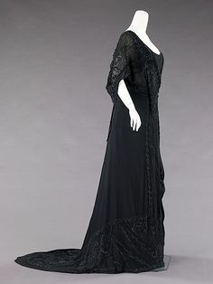 The elaborate but subtle beading on this mourning dress would have shimmered when new. The asymmetry of the charmeuse panel is indicative of the high fashion of the period. An example of extremely chic mourning attire for the evening, it features an element of subtle exposure: the beaded underpanel hidden by the charmeuse would have been revealed with the movement of the wearer