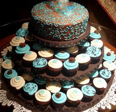 I like this idea - part of it is a cake (can be saved for first anniversary) and the rest is cupcakes.  The cupcake tower would need to be much higher and bigger, of course.
