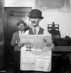 two-men-make-faces-and-read-a-yiddishlanguage-newspaper-printed-in-picture-Reading the Daily Jewish Courier, in Yiddish, 1930, Chicago.