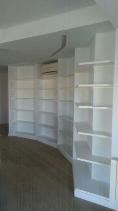 Elegante librería realizada con baldas de formas especiales lacadas en blanco.