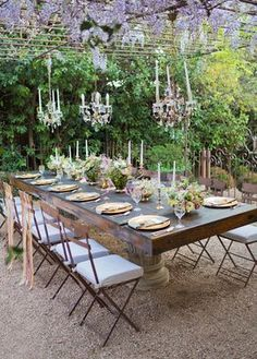Intimate can still be glam! Pergola, wisteria blooms, chandeliers, taper candles, matching chairs and dark brown wooden table...fab.