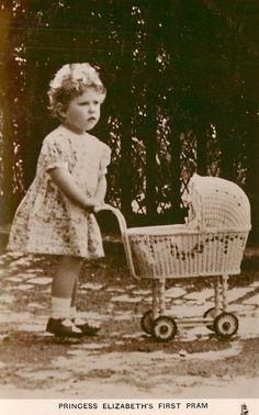 Princess Elizabeth (now Queen Elizabeth) pushing her doll's pram.