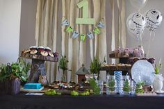 Woodland owl 1st birthday party theme. I like the child's name spelled out in scrabble tiles and the ceramic bird feeder filled with pastel peanut   m's and the serving trays cut from logs, very cool!