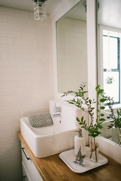 Beautiful, bright bathroom! Love the wood counter top #remodel works www.remodelworks.com
