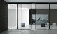 Valeria sliding doors design by Giuseppe Bavuso for Rimadesio. Black anodised aluminium frame and clear reflective glass.