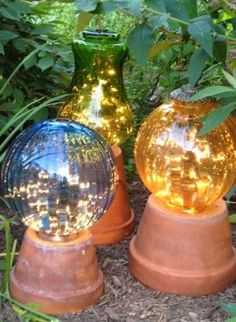 DIY - Garden lights made from flower pots and old lamp globes with strings of white lights in the globes. by teri-71