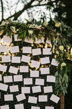 Modern wooden name card holder covered in garland: http://www.stylemepretty.com/california-weddings/winters-california/2016/08/17/this-sunset-wedding-is-take-your-breath-away-beautiful/ Photography: Retrospect Images - http://weddings.retrospectimages.com/home/