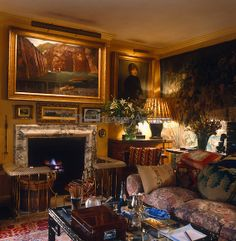 The yellow walls of this cosy sitting room in a London townhouse are decorated with gilt-framed paintings and a large tapestry ~ Mark Birley