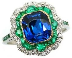 Art Deco sapphire, diamond, and emerald ring, circa 1915. A cushion-cut sapphire glows within a shaped cushion double border of emeralds and diamonds, and is further embellished by emerald line shoulders. Via Diamonds in the Library. by angelique