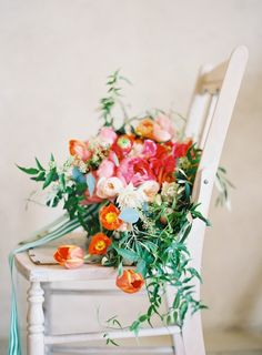 A vibrant cascading bouquet brimming with bright blooms and greenery and tied with a striped ribbon