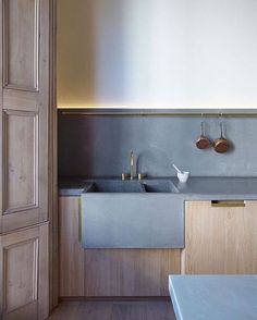 a peaceful minimalist kitchen with light-colored cabinets and concrete countertops and a backsplash