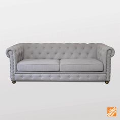 The Gordon Tufted Sofa from Home Depot's Home Decorators Collection adds classic style to any living room. This classic couch is as comfy as it is stylish, and comes in grey velvet, natural linen, and brown or black leather. The clean, vintage-inspired design helps elevate existing furniture and fits well with any style of interior design.