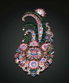 A QAJAR GOLD AND ENAMELLED GEM-SET TURBAN ORNAMENT, PERSIA OR GUJARAT, 19TH CENTURY. of oval form with an openwork floral medallion set with a large emerald and cut diamond petals surrounded by gem-set floral and foliate forms the curling crest surmounted with a half rosette and seed pearl and emerald fringing, the reverse enamelled with flowerheads, buds and scrolling vegetation, the rosette reverse with sun motif, suspension loops to reverse. 18.5cm.