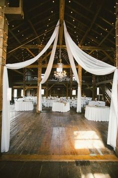 Add elegance to a barn wedding venue with crisp white draping and string lights - doesn't it make the room look wedding perfect. #SpringWedding #WeddingDrapes #WeddingDecor #WeddingInspiration #WeddingPlanning