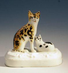 "Seated Cat with Laying Kitten. Tan, Black & White Calico Cat with a Black & White Spotted Kitten on a Base. Circa 1835-1840. 2-3/4"" x 2-1/2""."