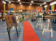 Red carpet walk through easels with paintings for sale
