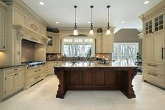 This massive white kitchen is dominated by a carved dark wood island with a marble countertop. Three pendant lights hang over the island.