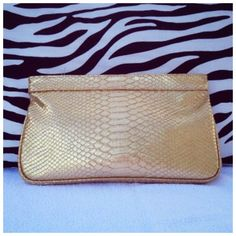 """Gold Snakeskin Guess Clutch NWOT Made by: Guess Snakeskin Print Gold Measurements: 7""""TallX12""""WideX1""""Thick Gold Metal Logo Zipper Pull. Fully lined in a Beautiful wine colored satin like material adorned with Guess Logo throughout. Also padded inside. This bag is New never used. Perfect for any occasion. Thank you for browsing my closet. Guess Bags Clutches & Wristlets"""