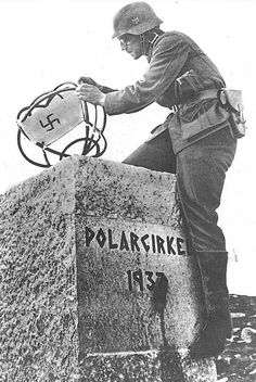 A German soldier attaches a Nazi flag to an obelisk denoting the edge of the Arctic Circle in northern Norway, May 1940. The pistol be is wearing appears to be a Polish ViS (or 'Radom') 9mm P35 (P). presumably captured in September 1939.