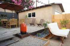 Modern outdoor room -- blend of wood slat fence, pea gravel, and river rock.
