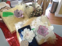 Fancy gift bows that include: sprigs of lavender, sea shell, tulle, fabric flowers, egg carton roses.