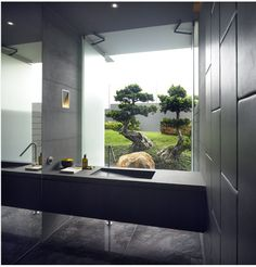 Bathroom with black tiled wall and black wash basin
