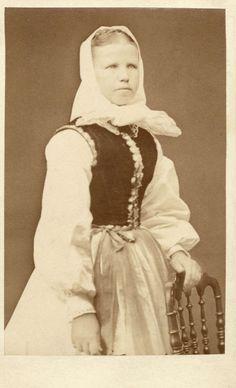 En ung flicka poserar i en folkdräkt från Blekinge, med vit huvudbonad knuten under hakan. Dresses, Fashion, Vestidos, Moda, Fashion Styles, Dress, Fashion Illustrations, Gown, Outfits