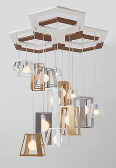 Lantern Helix chandelier by Think Fabricate | The lanterns are positioned in a cascading helix form hanging down from a geometric canopy that's made up of overlapping hexagonal shapes in two finishes. | retaildesignblog
