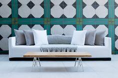 במרפסת יש ספה ארוכה, נשענת אל קיר שחופה באריחים גדולים ומאוירים כבמשיכות מכחול ( צילום: גדעון לוין )