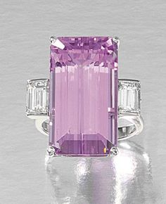 A KUNZITE AND DIAMOND RING.  Set to the centre with a step-cut kunzite, highlighted by step-cut diamonds to the shoulders