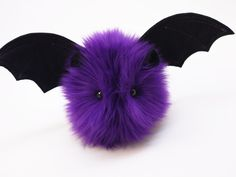 Hi, my name is Bella and I am a Fuzziggle. My fur is Dark Purple and super fluffy. I'm a small size bat; my body is about 4x4x5 inches, but my wingspan is 12 inches. I'm made of plush faux fur, my win