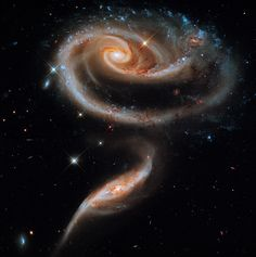 The interplay of their gravitational forces bends two spiral galaxies in this Hubble image.