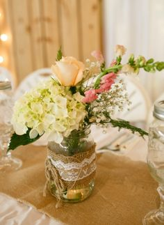 Small centerpieces can still be beautiful. Lace, burlap, and a mason jar hold expertly-arranged combination of flowers and greenery. | Tara Liebeck Photography Chesapeake Virginia