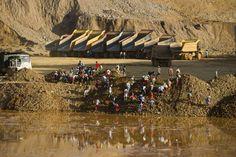 Decenas de mineros irregulares buscan restos del mineral de jade en los desechos arrojados por los volquetes.