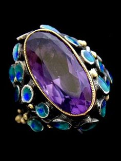 An Arts & Crafts amethyst, silver and gold ring in the style of Jessie Marion King. Centring an amethyst surrounded by asymmetric sprays of enamelled leaves with gold bud highlights, mounted in silver and gold. British. Circa 1900, unmarked.