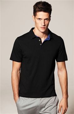 Black solid knit polo with blue placket trim. Cotton and Lyocell fabrication offer a luxurious feel and perfect fit.