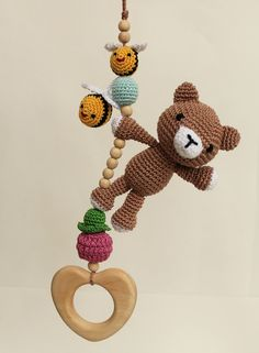 Bear & bees hanging toy, Car seat toy, Pram toy, stroller toy, crib toy, Baby Rattle, activity gym toy, gender neutral, juniper wood, mobile. This hanging toy features a crochet bear playing with flying bees and a raspberry. A carefree bear with playful bees will add happiness and fun to your baby's plays and trips. There are small bells inside the soft bear so it makes pleasant sounds when a baby plays with it. Crochet animals are handcrafted with a heart shaped wooden teething toy. The…