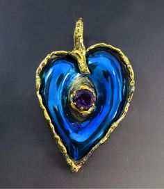 Titanium Heart Pendant beautifully shaped by using repoussé technique in the blue titanium. The purple Amethyst compliments the blue reflections. In contrast  the heart is surrounded by natural flowing silver edges fused in gold. #MeevisDesigns  Heart pendant / titanium  designer jewelry / bold statement fashion accessory