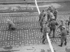 West Berlin policemen and East German soldiers face each other after a young girl made it across the border, 1955