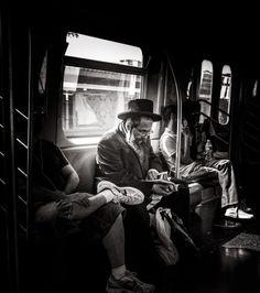 The Rabbi, New York City, USA – by Jake Metzger. Rabbi sitting on the train, reading.
