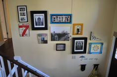 Love this stairwell or for a hallway. I love the framed keys. The Number 7 and the print of the relatives. Also the Family photo and framed intial.