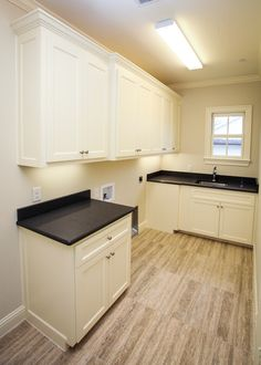 Village Cupboards for Gilbert Homes. Laundry room with custom cabinetry.