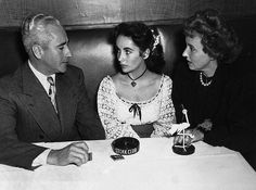 Original caption: ca.1949-New York, NY- Pretty and young cinema latest favorite Elizabeth Taylor flanked on both sides by her Mom and Dad, Mr. And Mrs. Francis Taylor, in the CUB room of Sherman Billingsley's Stork Club, where thay had luncheon upon their arrival from the west coast. They will take in some shows and the gals will do some shopping before returning to the coast to resume her picture making. 1949 New York, New York, USA