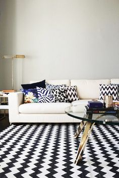 Living room with black and white rug white sofa patterned throw pillows and a glass coffee table  #currentlycoveting #holidays2015 #holidaze #holidaystyle