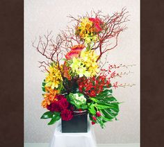 Description: Organic meets contemporary in this eclectic arrangement.  Bright yellow cymbidium orchids create a lattice with mango moccaras interwoven onto a manzanita branch floating atop deep red dahlia, tulips, celosia and heads of stark variegated green cabbage.  Large monstera leaves and looped aspidistra complete and envelope this spectacular piece of floral art.