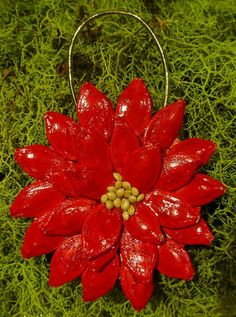 Poinsettia ornament made with pumpkin seed, millet seed and used cardboard.
