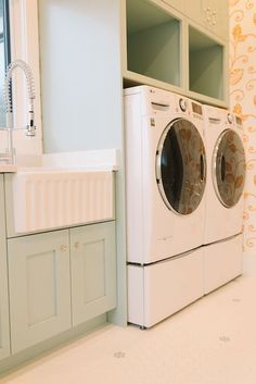 Lovely laundry room boasts front-load washer and dryer tucked under full height light green cabinets and cubbies beside a white rippled apron sink paired with a pull-out faucet. Laundry Closet, Laundry Room Storage, Storage Room, Closet Storage, Laundry Rooms, Laundry Room Layouts, Laundry Room Cabinets, Laundry Room Design, Washer And Dryer Pedestal