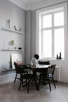 A round dining table in the corner of an open-plan living space with high ceilings. Dining Room Shelves, Dining Room Walls, Dining Room Design, Dining Nook, Dining Room Furniture, Black Furniture, Furniture Design, Black Round Dining Table, Swedish House
