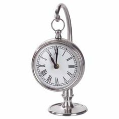 "Silver-finished brass table clock with a complementing stand.  Product: Table clockConstruction Material: BrassColor: SilverAccommodates: (1) AA Battery - not includedDimensions: 9.5"" H x 4.75"" W x 4"" D"
