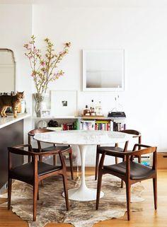 table tulipe blanche avec plateau en marbre, tapis en peau d'animal, murs beiges